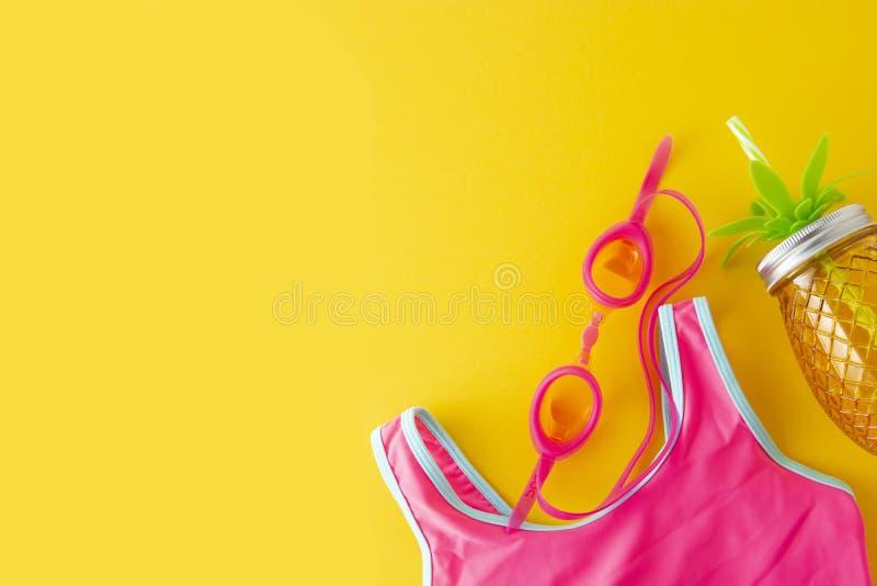 平的被放置的构成、夏天五颜六色的背景与桃红色泳装和海滩对象在黄色背景 复制文本的空间 免版税图库摄影