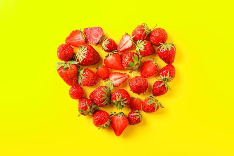 平的被放置的构成用以心脏的形式草莓在颜色背景 免版税图库摄影