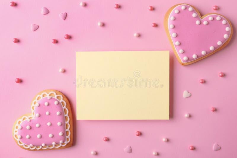 平的被放置的构成用心形的曲奇饼和在颜色背景的空插件 免版税库存图片