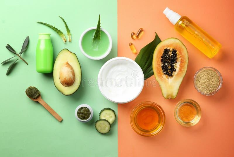 平的被放置的构成用果子和天然化妆品在颜色背景 免版税库存照片