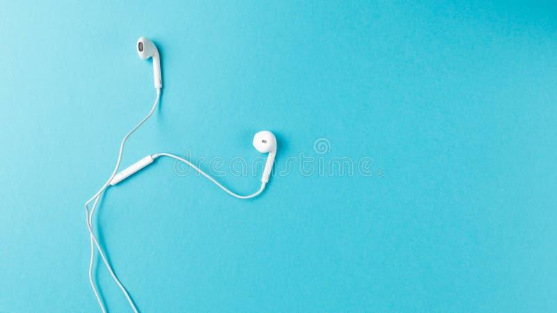 平的被放置的概念:在淡色背景的耳机 在蓝色背景,顶视图,copyspace的白色耳机 免版税库存图片