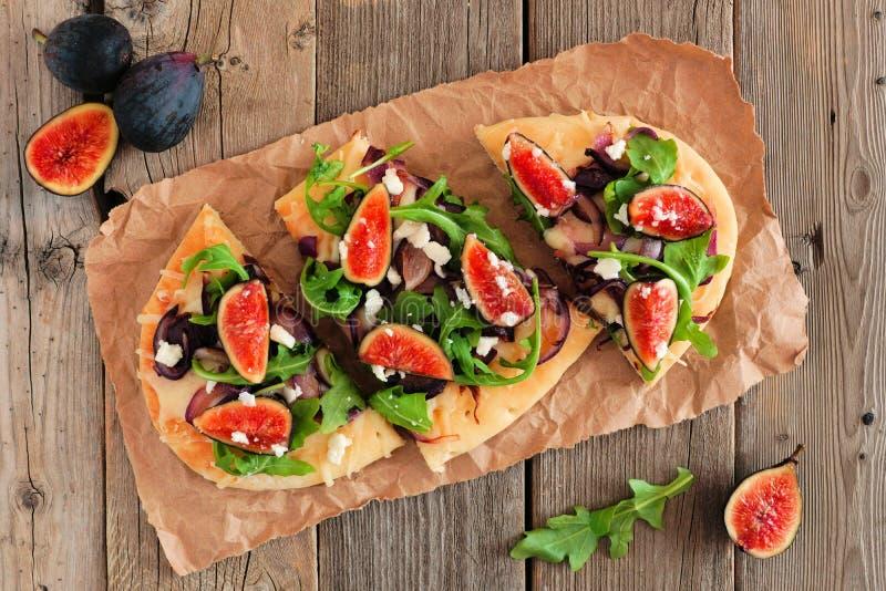 平的面包薄饼用无花果,芝麻菜,在土气木头的天花板 免版税库存图片