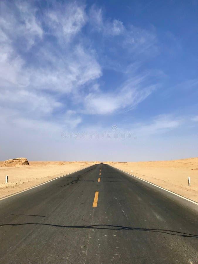 平直的沥青路,被修造在沙漠之间,没人路的 库存图片