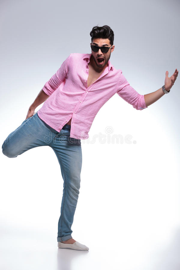 平衡与一条腿的年轻时尚人在他的手上 免版税库存照片