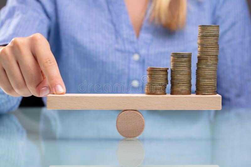 平衡与手指的女实业家被堆积的硬币 免版税图库摄影