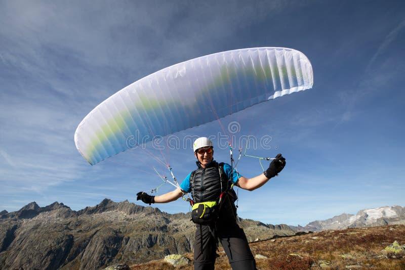 平衡他的在他的头上的滑翔伞飞行员的特写镜头滑翔伞 免版税库存照片