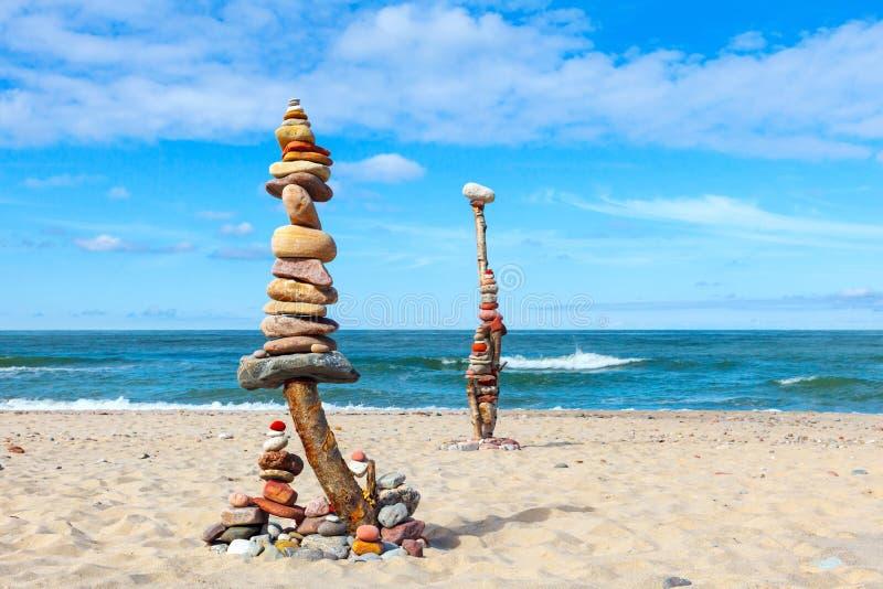 平衡和世故石头 晃动在蓝天和海背景的禅宗  库存照片
