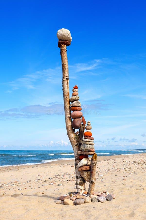 平衡和世故石头 晃动在蓝天和海背景的禅宗  免版税图库摄影