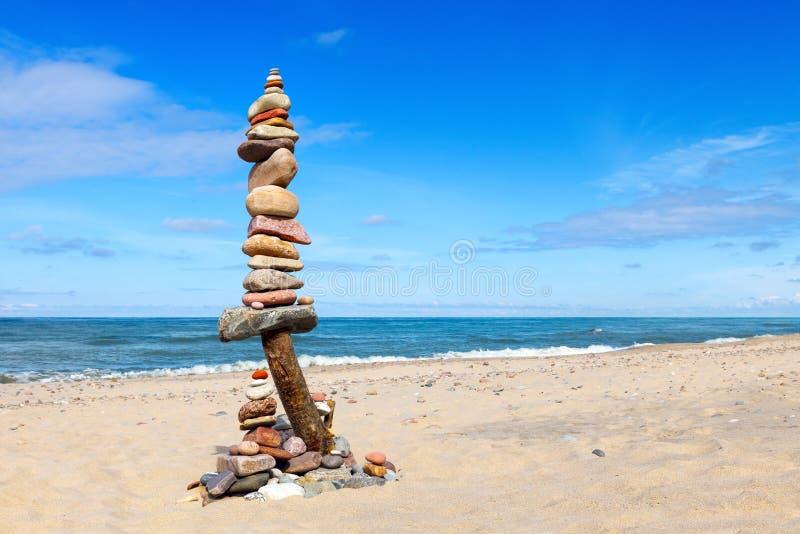 平衡和世故石头 晃动在蓝天和海背景的禅宗  库存图片