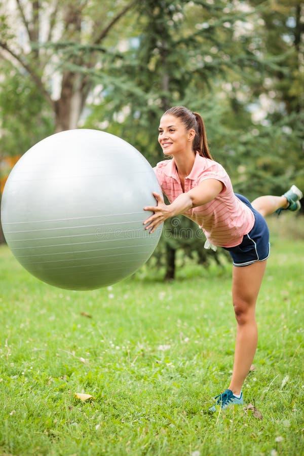 平衡在一条腿和拿着在她的胸口前面的愉快的年轻女人健身球 免版税图库摄影