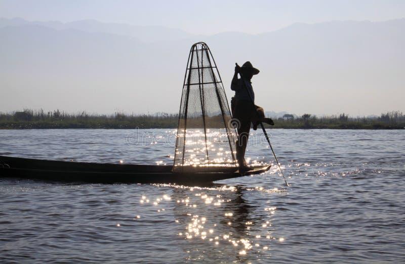 平衡在他的小船和荡桨用他的在Inle湖,缅甸的饲料的传统渔夫剪影 免版税库存照片