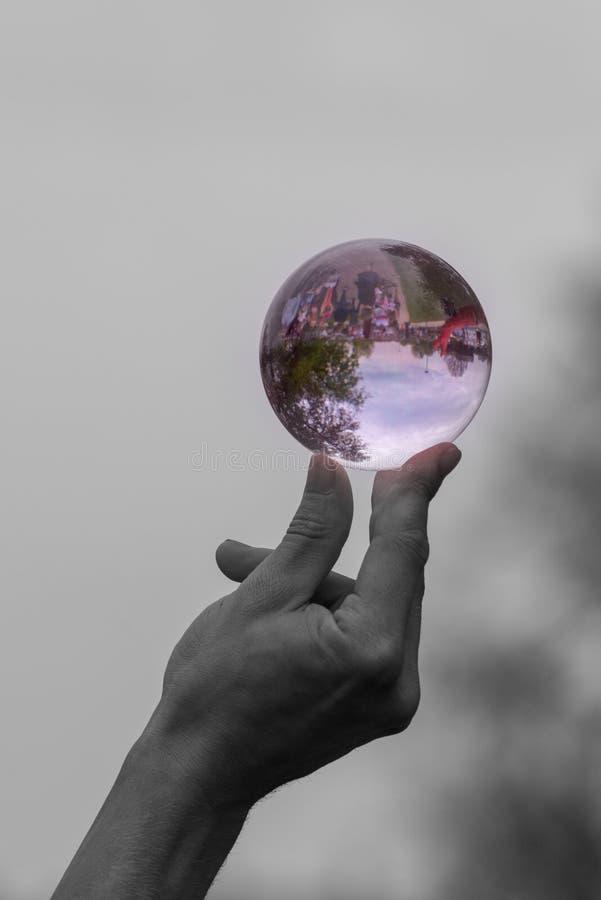 平衡在他的手指和拇指的末端的人的黑白图象紫色玻璃球形 图库摄影