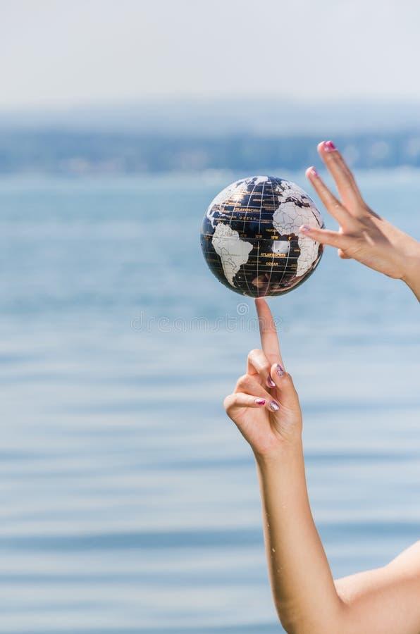 平衡在她的手指的年轻女人地球 库存照片