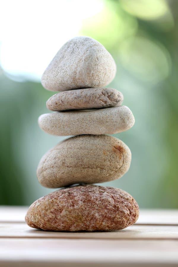 平衡在木地板上的岩石或禅宗石头和有自然绿色 库存图片