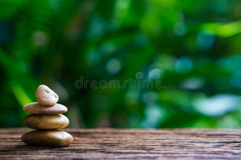 平衡在木头的禅宗石头有绿色自然bokeh背景 库存图片