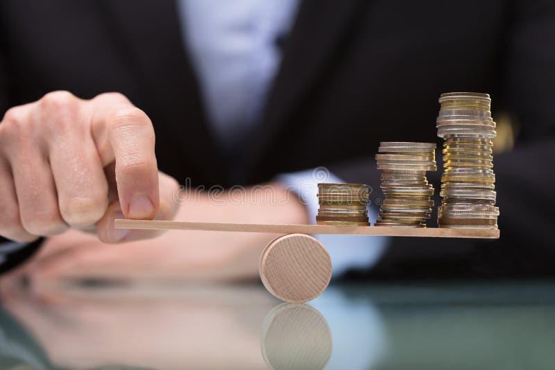 平衡在跷跷板的买卖人被堆积的硬币 库存图片