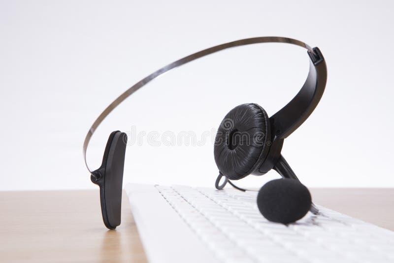 平衡在键盘的企业耳机 免版税图库摄影