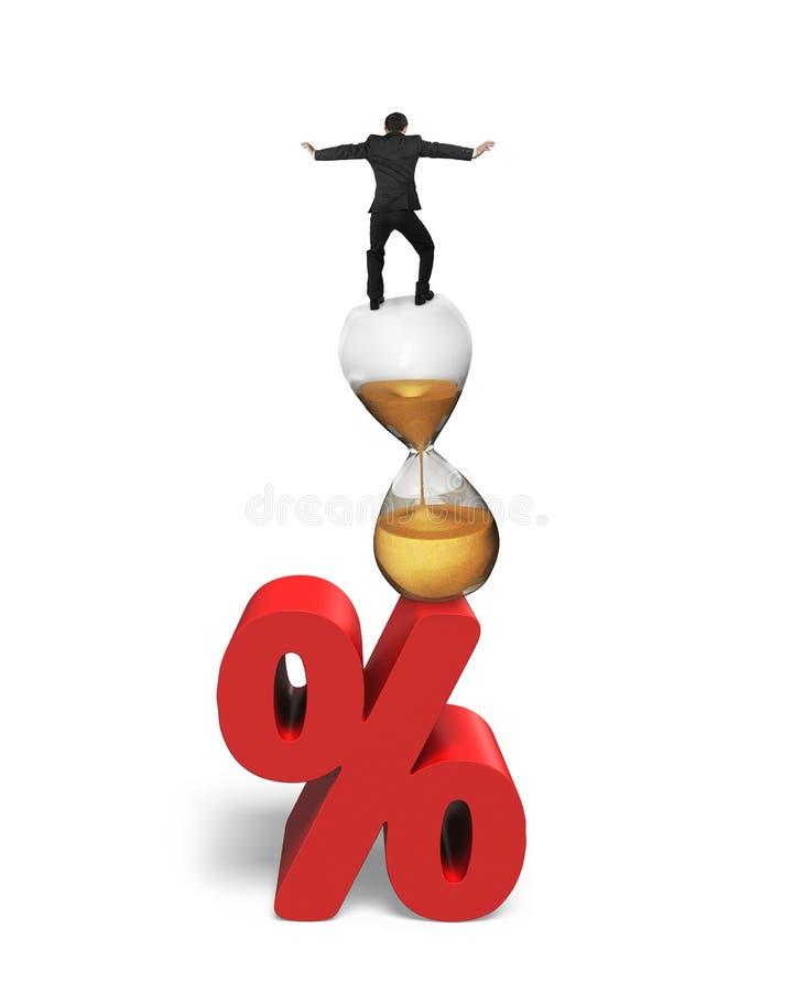 平衡在滴漏和红色百分率符号的商人 皇族释放例证