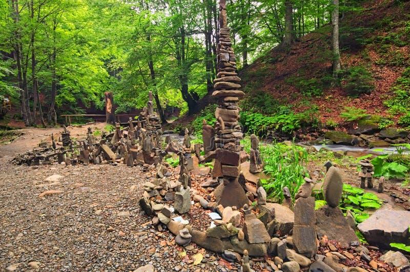 平衡的石头临近瀑布Shypit 堆石头在夏天早晨森林Zakarpattya,乌克兰里 免版税库存照片
