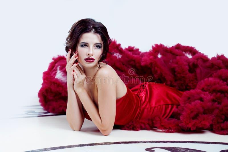 平衡的红色礼服秀丽深色的式样妇女 美好的时尚豪华构成和发型 免版税库存图片