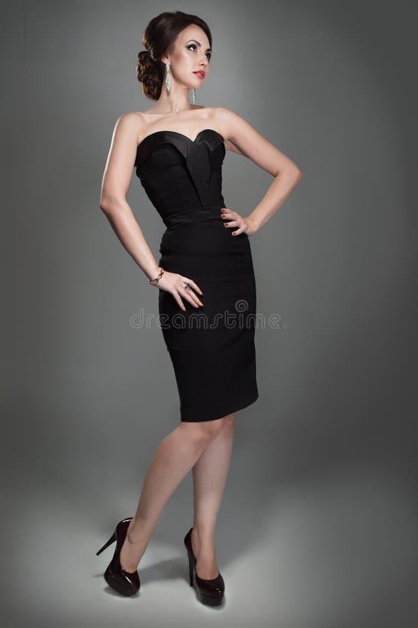 平衡的黑礼服妇女 免版税图库摄影