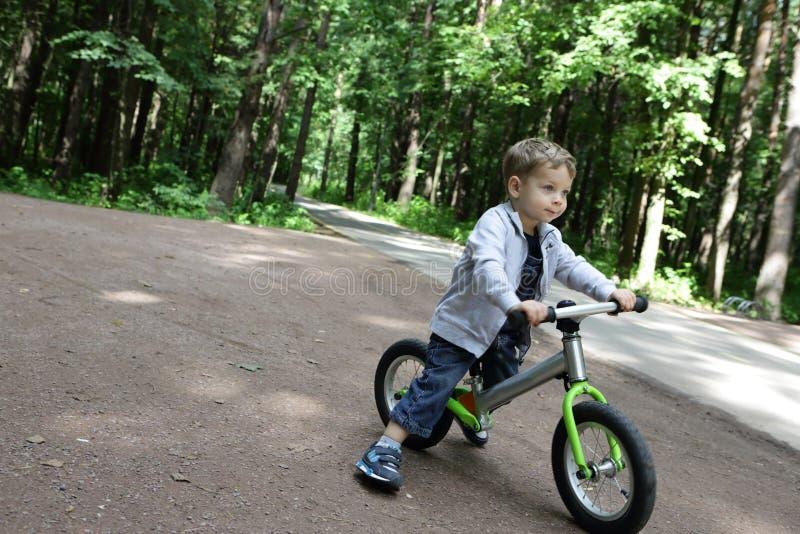 平衡自行车的男孩 免版税图库摄影