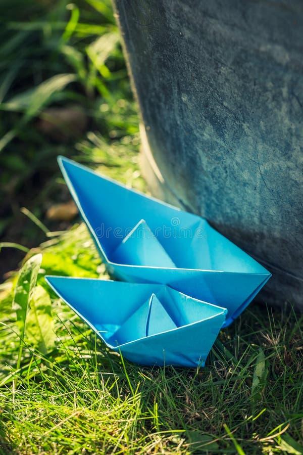 平静地漂浮在水的两条纸小船在庭院里 免版税库存照片