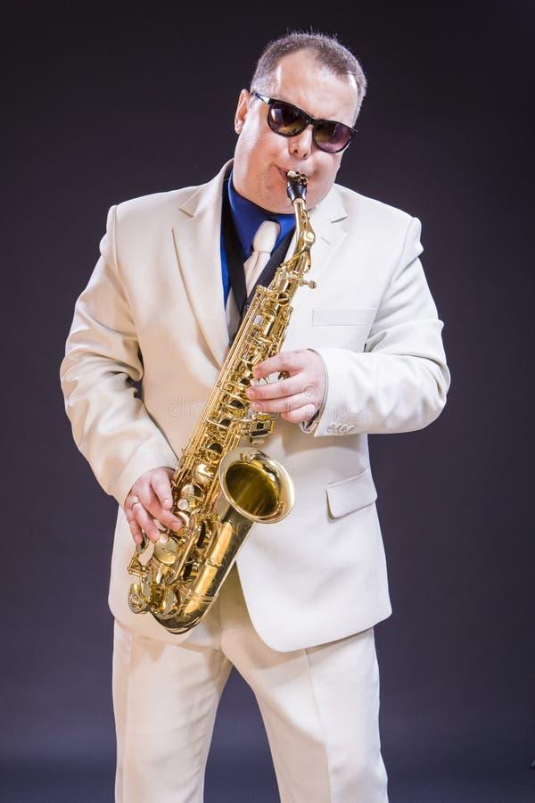 平静的白种人成熟萨克斯管吹奏者 免版税库存照片