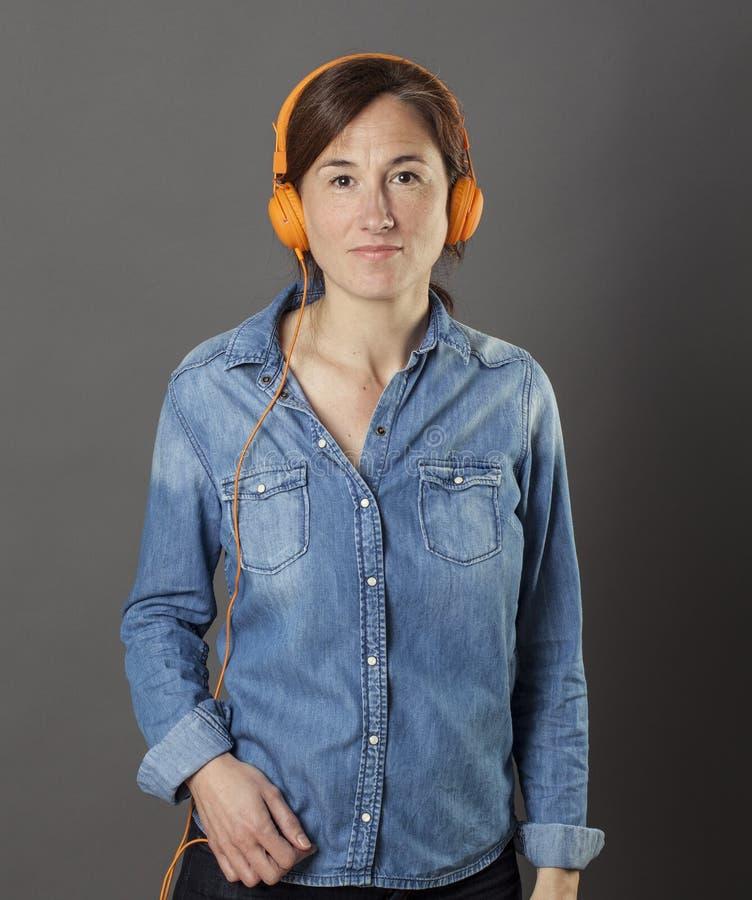 平静的美好的时髦的女人身分,放松在听到音乐 免版税库存照片
