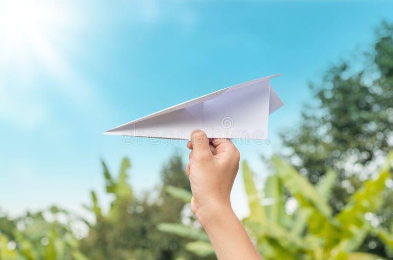 平面纸对于在农场和蓝天的儿童手 免版税库存图片