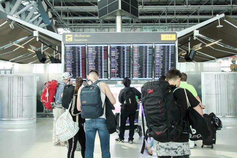 平面飞行乘客观看的时间表桌在素万那普airp的 免版税库存照片