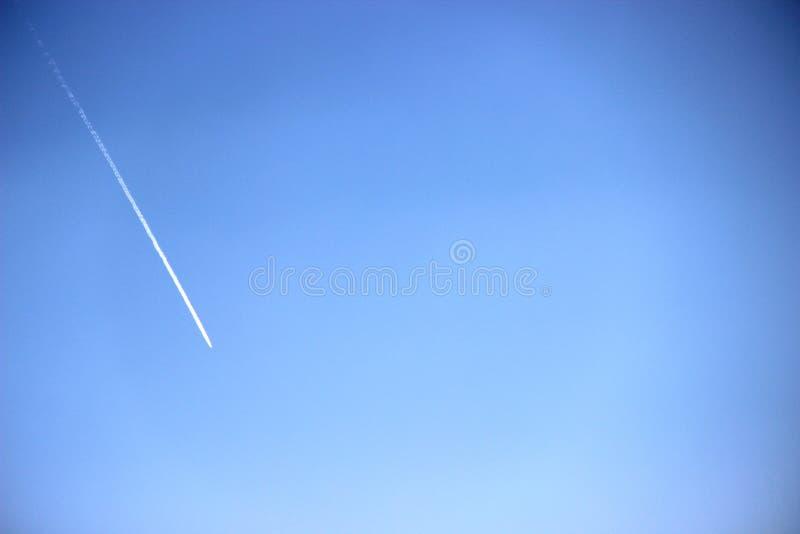 平面飞行的上流的白色踪影在天空蔚蓝的 库存照片