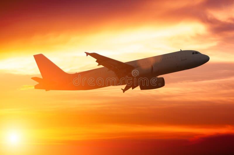 平面飞行的剪影在美好的日落的 库存照片