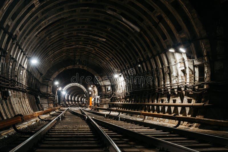 平直的圆地铁隧道连接到另一个隧道用管材和白光 图库摄影
