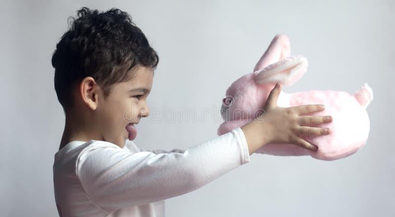 5年使用与豪华的兔宝宝玩具的可爱的小孩男孩 免版税库存图片