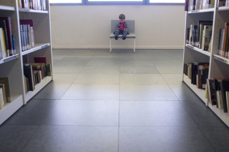 3年使用在智能手机的男孩WiFI在图书馆 库存图片