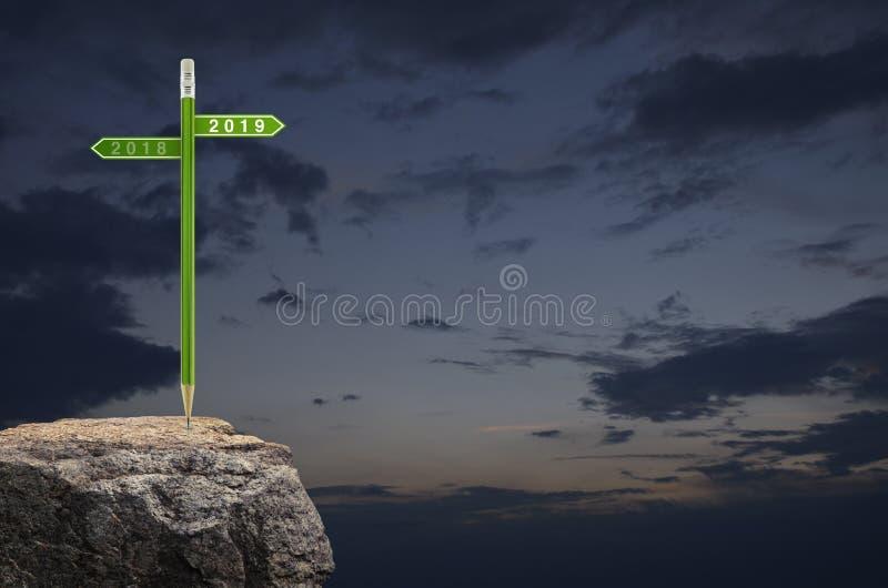 2019年和2018年有绿色铅笔的方向标板材在日落天空,经营战略计划概念的岩石山,愉快 免版税库存照片