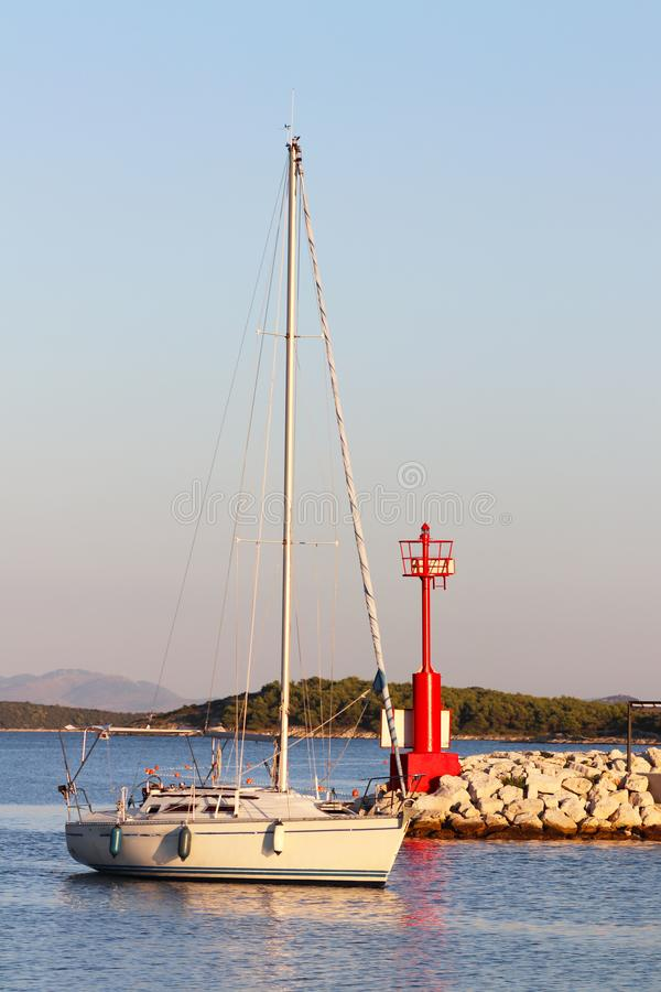 2003年巴伐利亚航行游艇回到通过表示入口的红色侧向烽火台的小游艇船坞 在海岛中的巡航 免版税库存图片