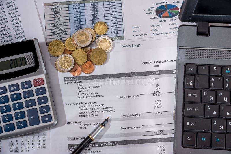 年度预算、市场研究和业务报告与膝上型计算机,欧洲票据、硬币和笔 库存照片