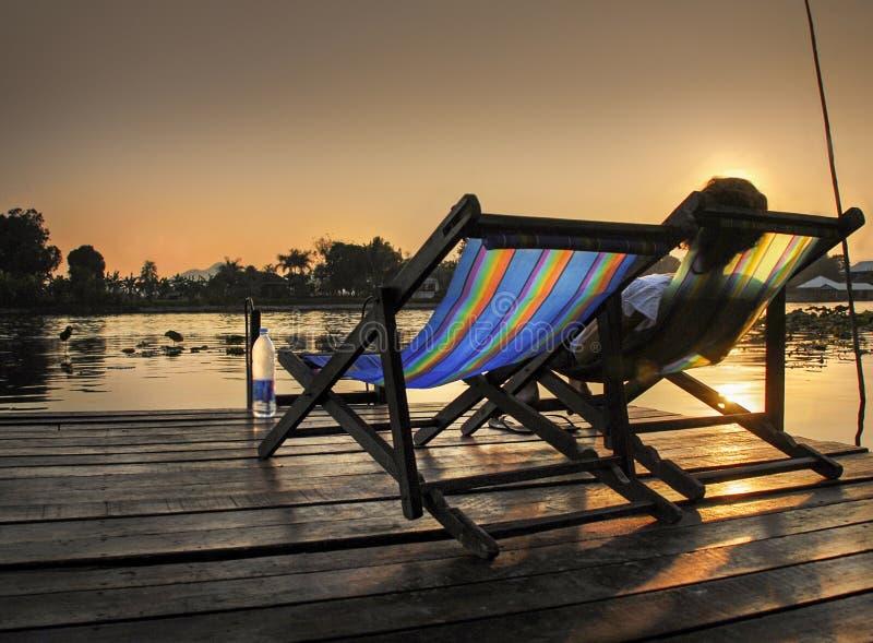 2011年沿购物车死亡2月kanchanaburi移动照片铁路铁路修理公司被采取的泰国跟踪工作者 妇女在轻便折叠躺椅放松在日落 在河Kwai旁边 免版税图库摄影