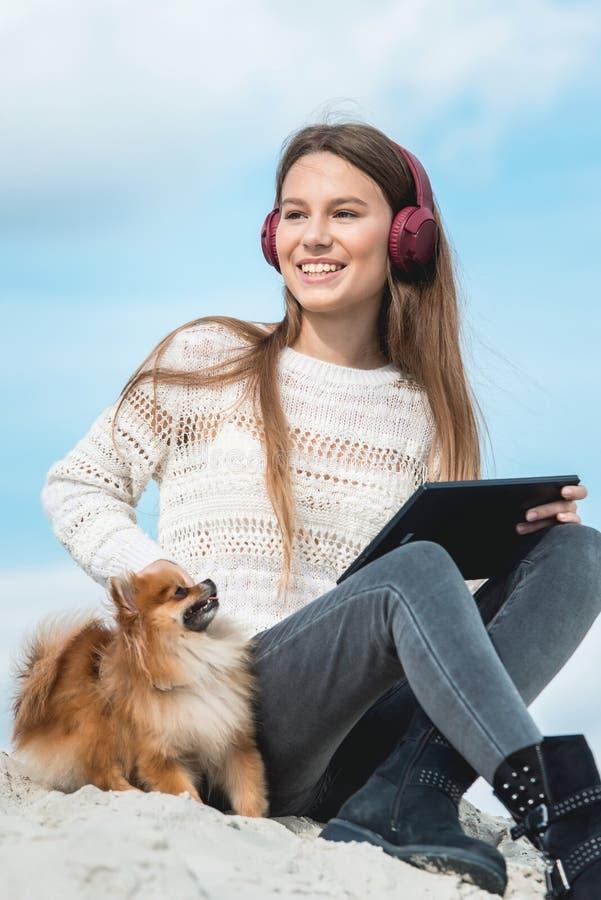 14年的女孩无线耳机听到从一智能手机的音乐的在海滩 蓝天 关闭 免版税库存图片