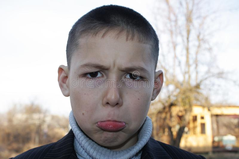 8年的男孩与黑眼睛的,做一副被触犯的鬼脸 库存照片