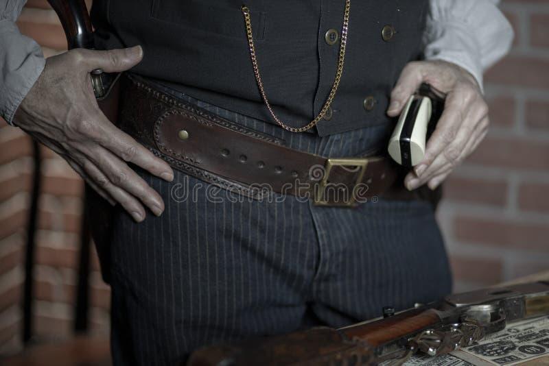 1885年的西部牛仔,手持手枪等着 库存图片