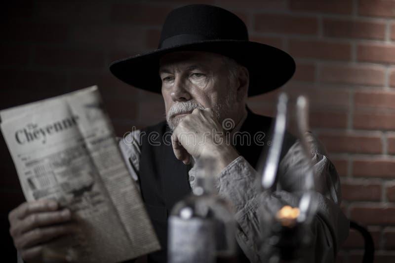 1885年老西部牛仔坐在报纸上 库存照片