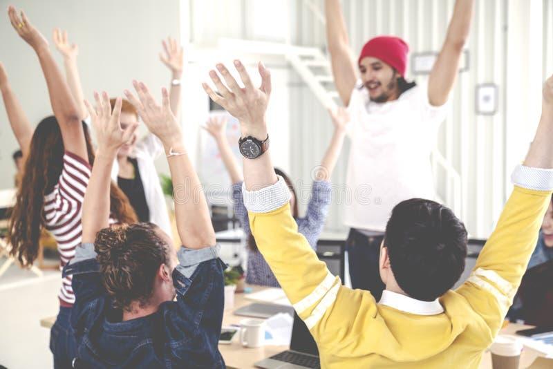 年轻不同种族的不同的创造性的亚洲小组挤作一团和高五只手在有成功的办公室车间或授权 库存图片