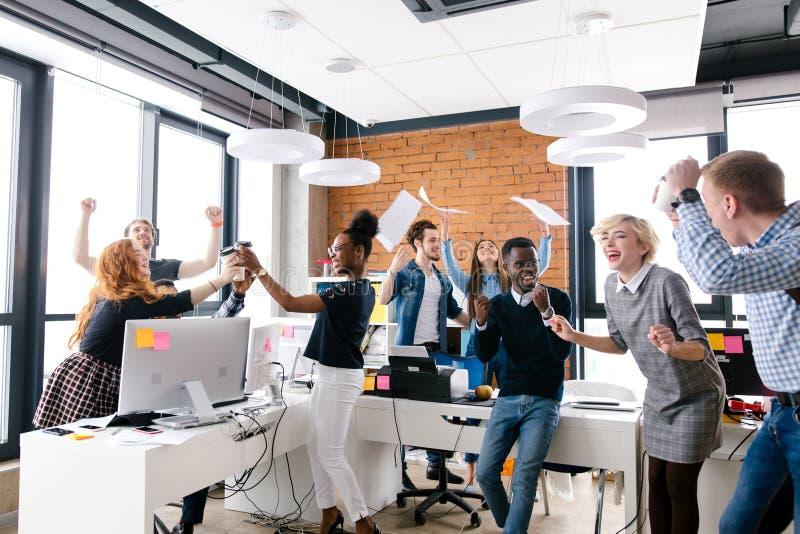 年轻不同种族的小组办公室工作者庆祝胜利 免版税库存图片