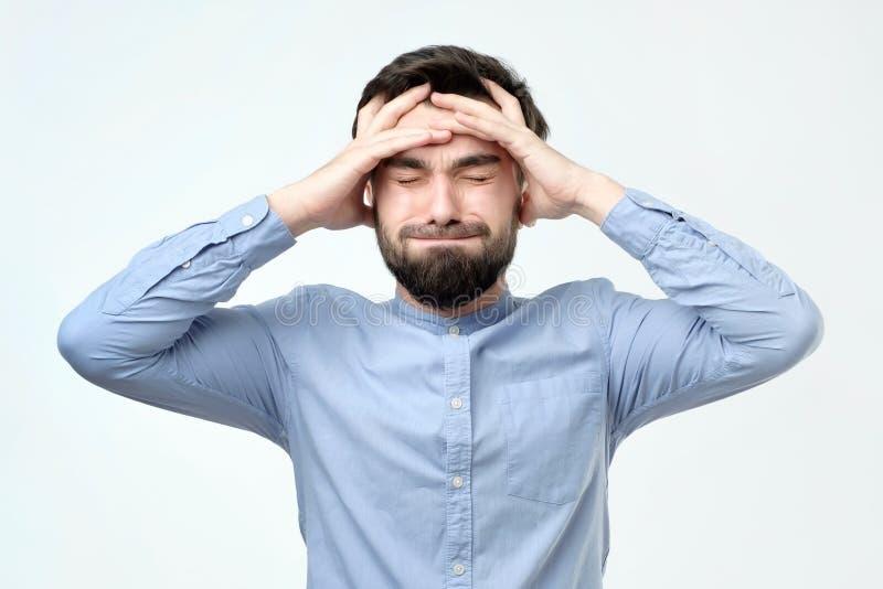 年轻不快乐的商人举行他的头、重音、头疼和失望概念 免版税库存图片