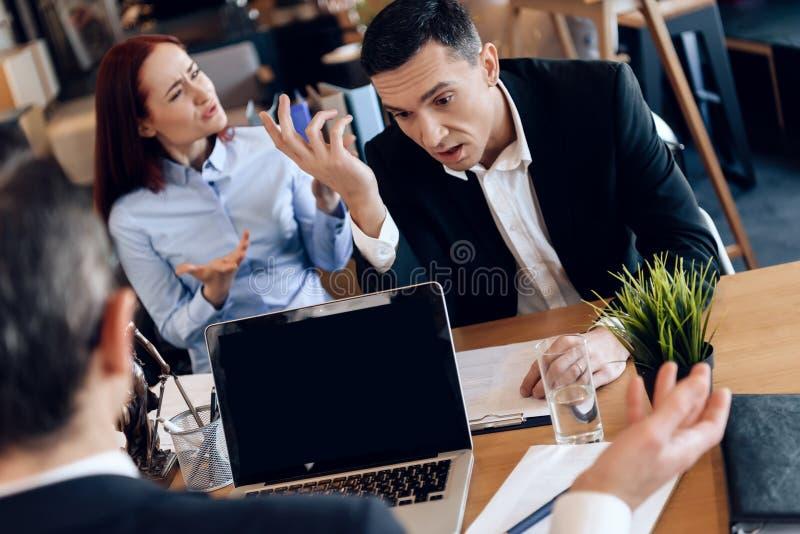 年轻与离婚的夫妇在离婚律师办公室情感地沟通 库存照片