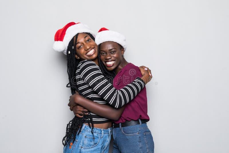年轻两名非洲妇女画象有圣诞老人在灰色背景隔绝的帽子拥抱的 图库摄影