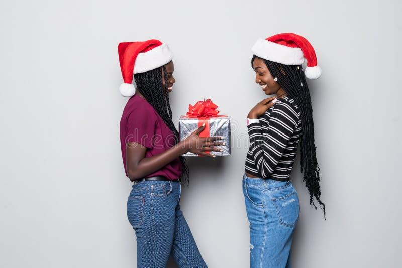 年轻两名非洲妇女画象有圣诞老人帽子在灰色背景隔绝的份额礼物的 免版税库存照片